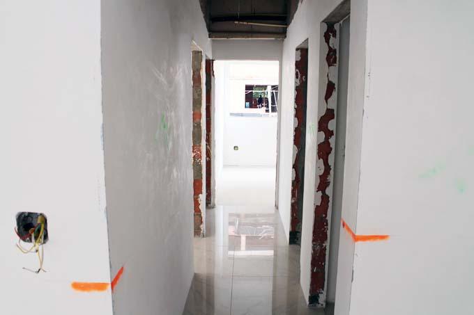 O gesso deve ficar plano e brilhando, assim como essa parede do lado esquerdo do corredor.